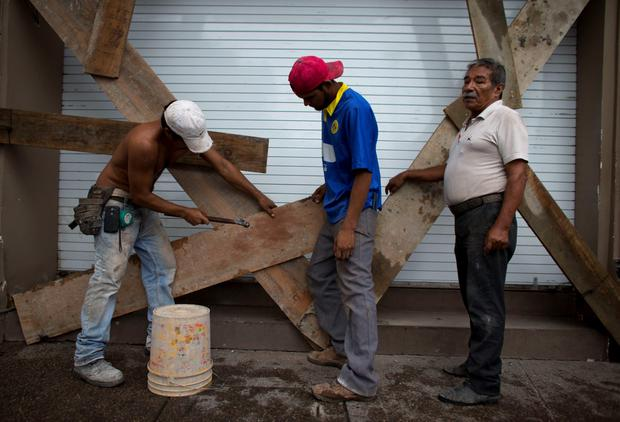 Men nail boards across the shutters of a waterfront business, as residents prepare for the arrival of Hurricane Patricia in Puerto Vallarta, Mexico, Friday, Oct. 23, 2015. (AP Photo/Rebecca Blackwell)