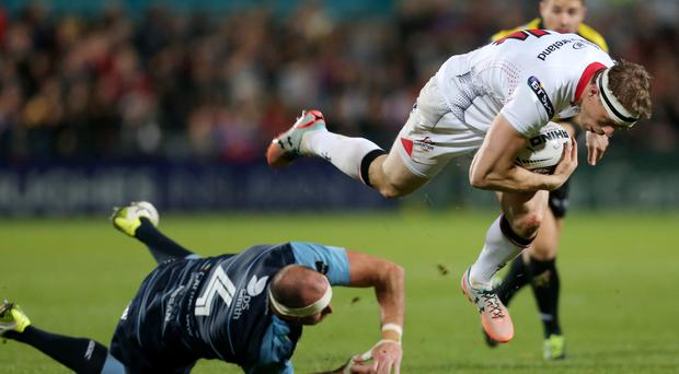 Up in the air: Andrew Trimble is impeded as he charges forward for Ulster against Cardiff