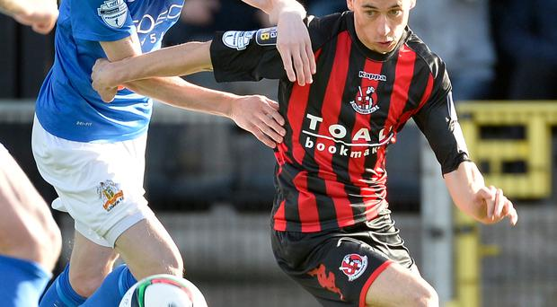 On the run: Paul Heatley holds off Rhys Marshall of Glenavon