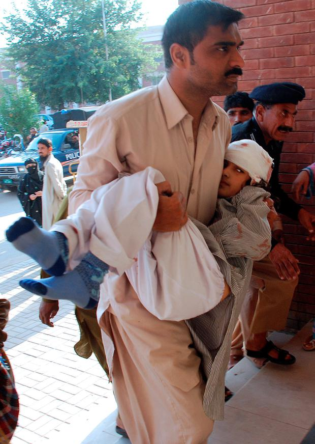 A Pakistani man carries an injured student at a hospital after an earthquake in Sargodha on October 26, 2015. A powerful 7.5 magnitude earthquake killed at least 70 people as it rocked south Asia, including 12 Afghan girls crushed to death in a stampede as they tried to flee their collapsing school. Thousands of frightened people rushed into the streets in Afghanistan, Pakistan and India as the quake shook a swathe of the subcontinent. AFP PHOTO / SHAHID BUKHARISHAHID BUKHARI/AFP/Getty Images