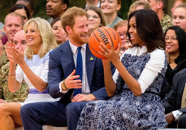 First lady Michelle Obama, accompanied by Jill Biden, left, reacts as Britain's Prince Harry hands her the basketball as the conclusion of a game of wheelchair basketball by wounded servicemen and veterans at Fort Belvoir military base, Wednesday, Oct. 28, 2015 in Fort Belvoir, Va. The event was held in support of the Invictus Games Orlando 2016. (AP Photo/Andrew Harnik)
