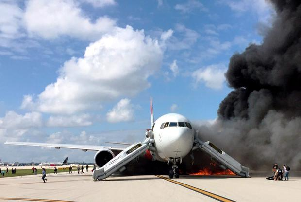 Passengers evacuate from a plane on fire at Fort Lauderdale airport, Florida on October 29, 2015. AFP/Getty Images