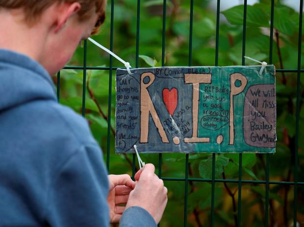 Pupils attach tributes to the gates at Cults Academy in Aberdeen where 16 year old Bailey Gwynne died after being stabbed. PA