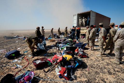 In this Russian Emergency Situations Ministry photo, made available on Monday, Nov. 2, 2015 Egyptian soldiers collect personal belongings of plane crash victims. (Russian Ministry for Emergency Situations photo via AP)