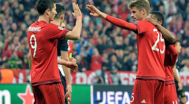 High five: Bayern's Thomas Mueller (right) celebrates his goal with Robert Lewandowski as Arsenal are crushed in Munich