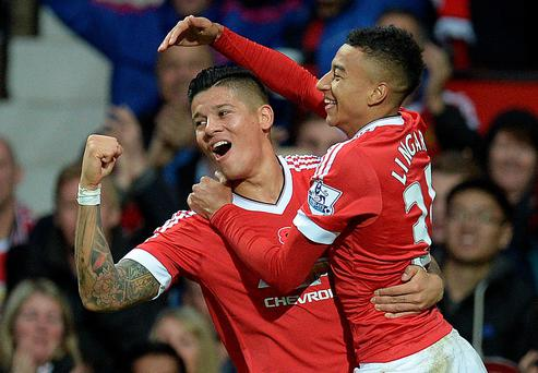 Manchester United's English midfielder Jesse Lingard (R) celebrates scoring his team's first goal with Manchester United's Argentinian defender Marcos Rojo