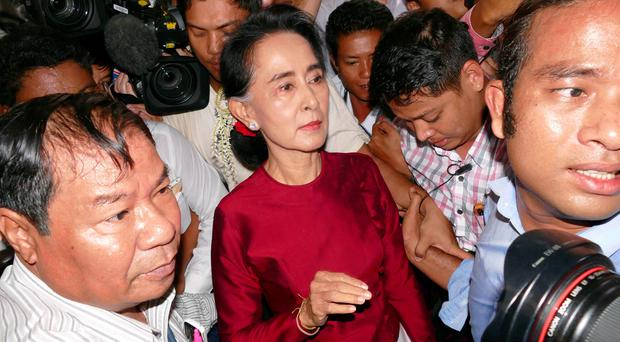 Myanmar opposition leader Aung San Suu Kyi, center, leaves after casting her ballot at a polling station in general election Sunday, Nov 8, 2015, in Yangon, Myanmar. (AP Photo/Khin Maung Win)