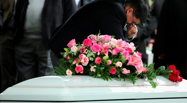 A relative grieves over the coffin of screen legend Maureen O'Hara