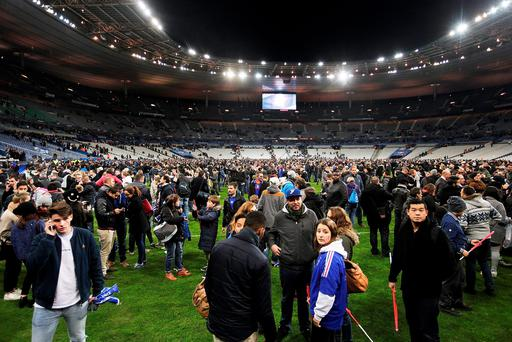 PARIS, FRANCE - NOVEMBER 13: Spectators gather on the pitch after news of the bombing and terrorist attacks in Paris reaches the fans after the International Friendly match between France and Germany at the Stade de France on November 13, 2015 in Paris, France. (Photo by Adam Pretty/Bongarts/Getty Images)