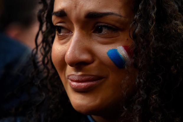 A woman weeps at a vigil held by the local French community in Sydney on November 14, 2015, as Australians express their solidarity with France following a spate of coordinated attacks that left 128 dead and 180 injured in Paris late on November 13. Both the Opera House and the Sydney Town Hall were bathed in the French colours and New South Wales state Premier Mike Baird said he had also asked for a French flag to fly over the city's famous harbour bridge. AFP/Getty Images