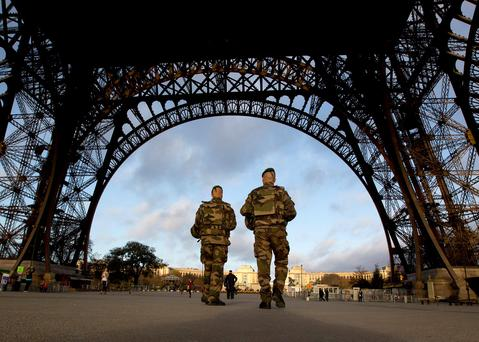 French soldiers patrol at the Eiffel Tower which remained closed on the first of three days of national mourning in Paris, Sunday. (AP Photo/Peter Dejong)