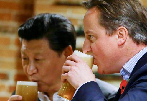 Prime Minister David Cameron (right) drinks a pint with Chinese President Xi Jinping Pic Kirsty Wigglesworth/PA Wire
