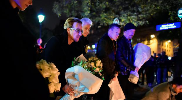 Bono and band members from the band U2 place flowers on the pavement near the scene of yesterday's Bataclan Theatre terrorist attack on November 14, 2015 in Paris, France. At least 120 people have been killed and over 200 injured, 80 of which seriously, following a series of terrorist attacks in the French capital. (Photo by Jeff J Mitchell/Getty Images)