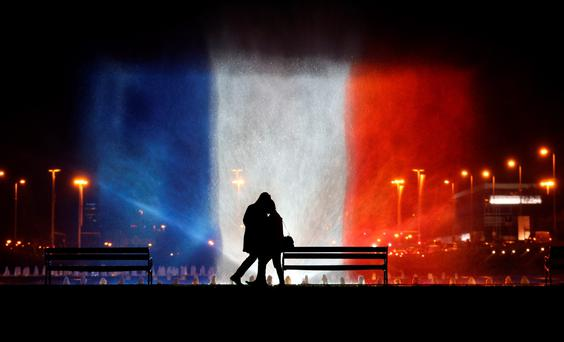 A young couple stands in front of illuminated waters with the colors of the French national flag on November 16, 2015 to pay tribute to victims of the attacks claimed by Islamic State which killed at least 129 people and left more than 350 injured on November 13. AFP PHOTO / STRINGERSTR/AFP/Getty Images