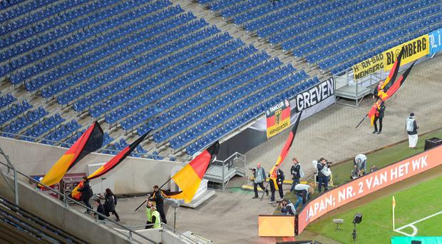 Helpers take off German flags from the stadium after the friendly football match Germany vs the Netherlands was called off for 'security reasons' in Barsinghausen on November 17, 2015. AFP/Getty Images