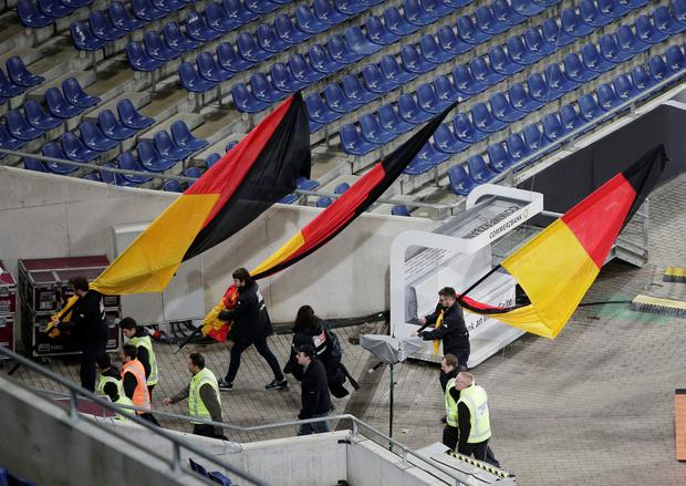 German flags are carried out of the stadium as the soccer friendly between Germany and the Netherlands was cancelled in Hannover, Germany, Tuesday, Nov. 17, 2015. (AP Photo/Michael Sohn)