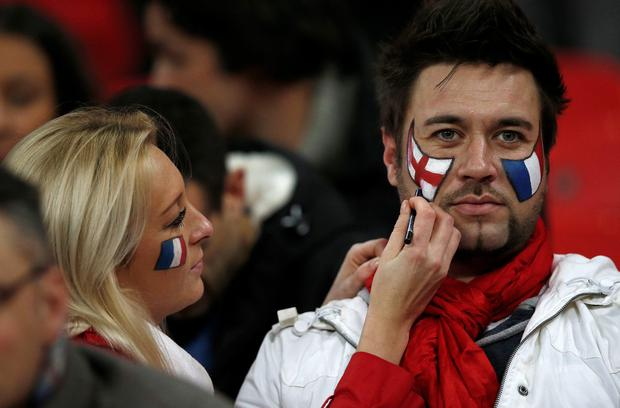 Football fans draw English and French flags on their faces before the start of the international friendly match between England and France at Wembley Stadium in west London on November 17, 2015. AFP/Getty Images