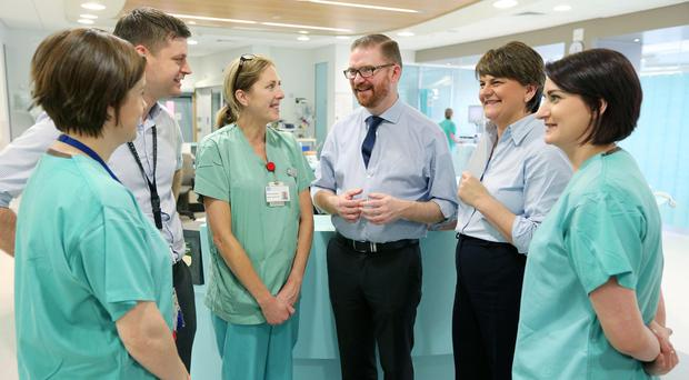 Health Minister Simon Hamilton and Finance Minister Arlene Foster with hospital staff Shauna Lynan, Dr David Hendron, Angela Richards and Laura Humphries at the ICU at the Ulster Hospital yesterday