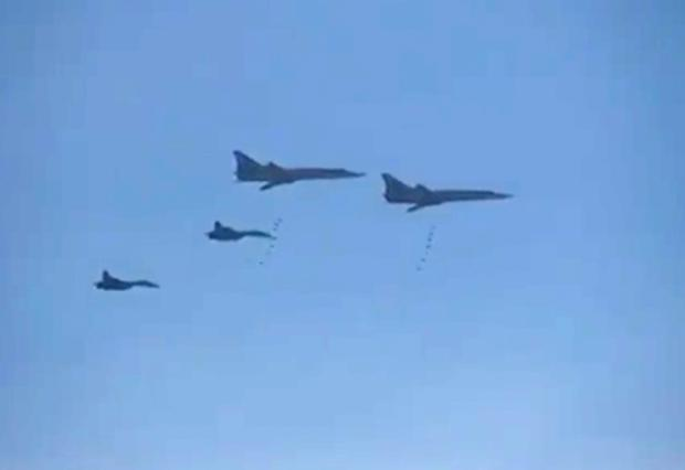 In this photo made from the footage taken from Russian Defense Ministry official web site on Tuesday, Nov. 17, 2015, Russian Tu-22 bombers escorted by the Su-27s fighter jets drop bombs on a target in Syria. Russia's defense minister said its warplanes have fired cruise missiles on militant positions in Syria's Idlib and Aleppo provinces. The Islamic State group has positions in Aleppo province; Idlib has the presence of the Nusra militant group. (AP Photo/ Russian Defense Ministry Press Service)
