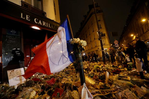 People gather at a makeshift memorial for a tribute to the victims of a series of deadly attacks in Paris, in front of the Carillon cafe on rue Bichat and rue Alibert in Paris on November 20, 2015. AFP PHOTO/THOMAS SAMSON/Getty Images.