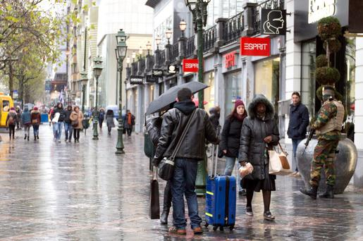 A Belgian Army soldier , right, patrols on a busy shopping street in Brussels on Saturday, Nov. 21, 2015. Belgium raised its security level to the highest degree on Saturday as the manhunt continues for extremist Salah Abdeslam who took part in the Paris attacks. (AP Photo/Virginia Mayo)