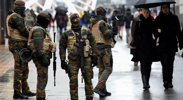 Soldiers patrol a pedestrian shopping street in Brussels on November 21, 2015. All metro train stations in Brussels will be closed on November 21, the city's public transport network said after Belgium raised the capital's terror alert to the highest level, warning of an