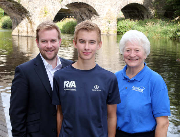 Water boy: Dame Mary Peters and Stuart Carson from Rainbow Communications congratulate young sailor Conor Quinn (centre) on his Rainbow Sports Award