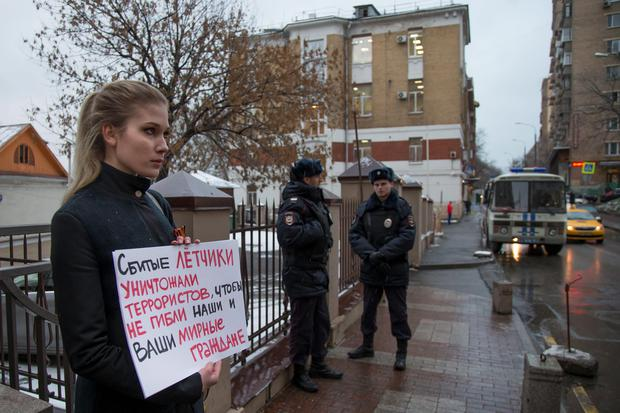 A woman holds a poster as she pickets the Turkish Embassy in Moscow, Russia, Tuesday, Nov. 24, 2015. Russian President Vladimir Putin on Tuesday has called Turkeys decision to down a Russian jet near the Syria border a stab in the back. The poster reads : The pilots that were shot down, were fighting with terrorists, to save your and our civilians. (AP Photo/Alexander Zemlianichenko)