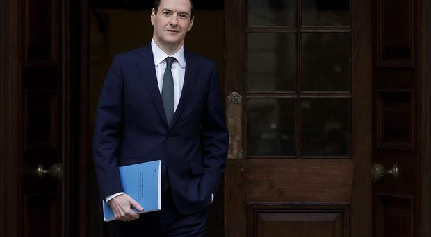 Chancellor of the Exchequer George Osborne carries a copy of his Autumn Statement as he leaves the Treasury in London. AFP PHOTO / TIM IRELAND / POOLTim Ireland/AFP/Getty Images
