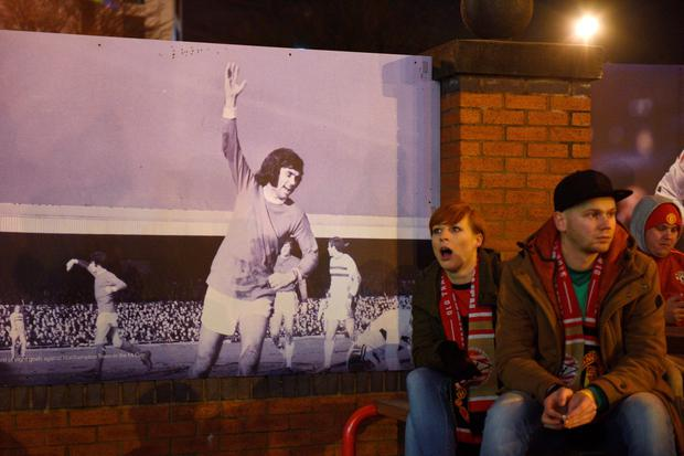 Football fans sit next to a poster of former Manchester United and Northern Ireland footballer George Best on the 10th anniversary of his death, outside Old Trafford Stadium in Manchester, north west England, on November 25, 2015, ahead of the UEFA Champions League Group B football match between Manchester United and PSV Eindhoven. AFP/Getty Images