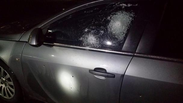 The unmarked police car was riddled with bullets.