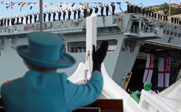 Queen Elizabeth II waves to British Royal Navy crew members performing a salute on the HMS Bulwark amphibious assault ship(Photo by Toby Melville - Pool/Getty Images)