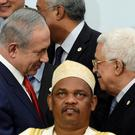 Israeli Prime Minister Benjamin Netanyahu (L) talks with Palestine's president Mahmud Abbas (R) behind Comoros' President Ikililou Dhoinine during the family photo during the COP21, United Nations Climate Change Conference, in Le Bourget, outside Paris, on November 30, 2015. AFP/Getty Images