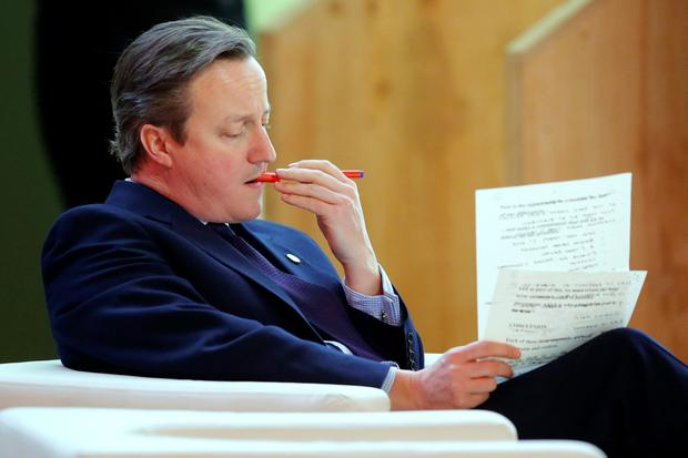 British Prime Minister David Cameron goes over some paperwork prior to addressing world leaders at the COP21, United Nations Climate Change Conference, in Le Bourget, outside Paris, Monday, Nov. 30, 2015. (AP Photo/Michel Euler)