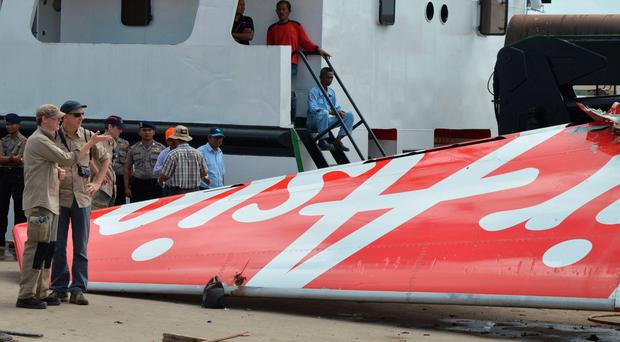 In this file photograph taken on January 12, 2015, foreign investigators (L) examine the recovered tail of the AirAsia flight QZ8501 in Kumai. (AFP Photo/FILESSTR/AFP/Getty Images)
