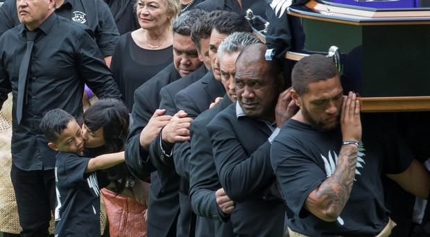 The body of former All Black Jonah Lomu is carried off the pitch as Nadene Lomu, bottom, second left, widow of Lomu, kisses her son Dhyreille Lomu, bottom left, at the conclusion of the public memorial for the former All Black at Eden Park in Auckland, New Zealand, Monday, Nov. 30, 2015. Thousands of mourners, many wearing replicas of Lomu's No. 11 jersey, crowded the park for the final public memorial for the rugby great who died Nov. 18 aged 40. Standing behind them are: Nadane Lomu's father Mervyn Lomu, and mother Lois Kuiek. (Hannah Peters/Pool Photo via AP)