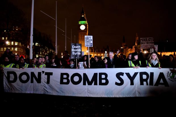 Protesters stand behind a banner that reads 'Don't bomb Syria' during a demonstration against British military action in Syria outside the Houses of Parliament in London on December 1, 2015. AFP/Getty Images