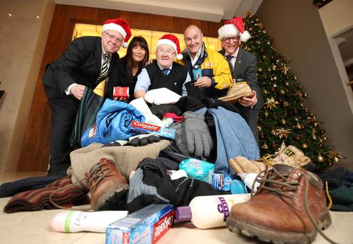 Launching the Clothes for Christmas appeal are Peter McVerry from U105, Kathy Henry, Council for the Homeless, bus driver Paul Doyle, Joe Hyland, SOS Bus NI and James McGinn from Hastings Hotels.