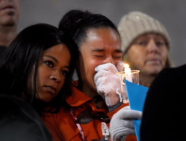 A woman cries during a candlelight vigil for shooting victims at San Manuel Stadium in San Bernardino, Calif. A husband and wife opened fire on a holiday banquet, killing multiple people on Wednesday. Hours later, the couple died in a shootout with police. (AP Photo/Mark J. Terrill)