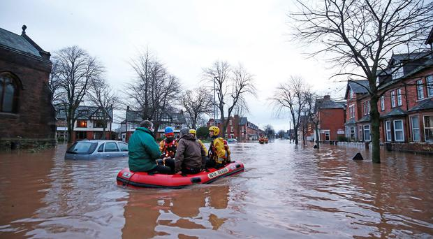 Emergency workers use a boat in floodwater on Warwick Road in Carlisle, after heavy rain from Storm Desmond tore through Britain, bringing strong winds and heavy rain which caused Cumbria to declare a major incident. Owen Humphreys/PA Wire.