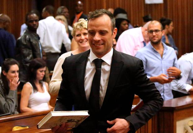 Former Paralympic champion Oscar Pistorius (C) smiles as he leaves the North Gauteng High Court in Pretoria, South Africa, after his bail hearing, on December 8, 2015. AFP / POOL / SIPHIWE SIBEKOSIPHIWE SIBEKO/AFP/Getty Images