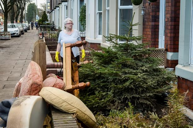 People clear their houses of water damaged property, including a Christmas tree, as the clean-up begins on Warwick Road after the floods in Carlisle. PRESS ASSOCIATION Photo. Picture date: Tuesday December 8, 2015. See PA story WEATHER Winter. Photo credit should read: Ben Birchall/PA Wire