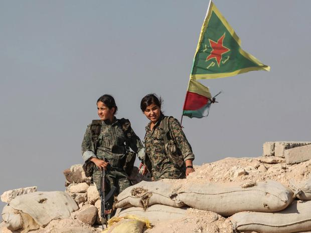 Kurdish People's Protection Units, or YPG women fighters stand near a check point in the outskirts of the destroyed Syrian town of Kobane, also known as Ain al-Arab, Syria. June 20, 2015. Getty Images