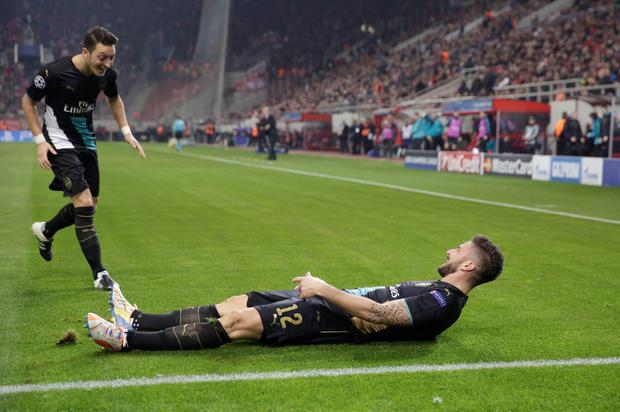 Arsenal's Olivier Giroud, right, celebrates with his teammates Mesut Ozil after scoring during a Champions League Group F soccer match between Olympiakos and Arsenal at the Georgios Karaiskakis stadium in Piraeus port, near Athens, Wednesday, Dec. 9, 2015. (AP Photo/Petros Giannakouris)