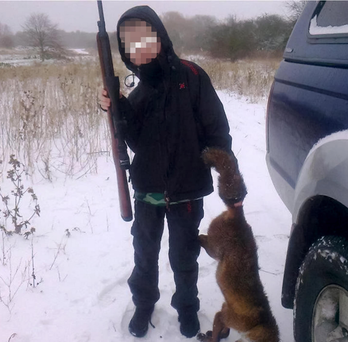 A child poses with a rifle and a dead fox in one of the alarming pictures