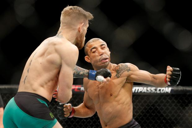 Conor McGregor, left, fights Jose Aldo during a featherweight championship mixed martial arts bout at UFC 194, Saturday, Dec. 12, 2015, in Las Vegas. (AP Photo/John Locher)