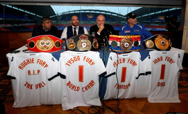Tyson Fury (second left) and his management team with his world title belts