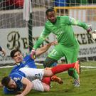 Safe hands: Alvin Rouse seizes on the ball as Linfield duo Jimmy Callacher and Mark Stafford crash to the floor