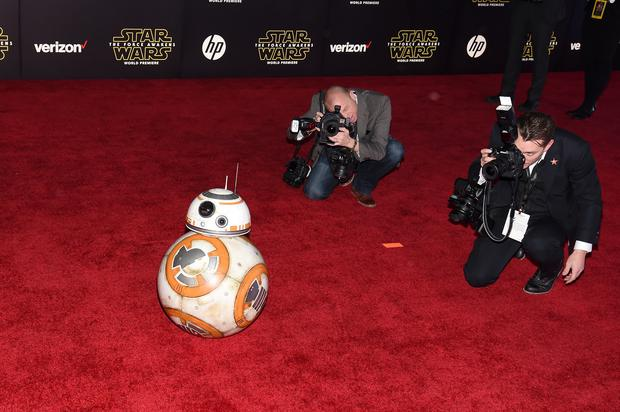 HOLLYWOOD, CA - DECEMBER 14: Photographers take pictures of BB-8 as it rolls down the red carpet during the premiere of Walt Disney Pictures and Lucasfilm's