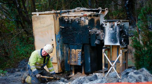 Electrical engineers at the scene of an overnight arson attack in the Ballygomartin area of North Belfast where over 2500 homes were left with out power in Belfast , Northern Ireland on December 18 ( Photo by Kevin Scott / Belfast Telegraph )